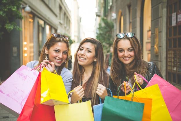 Giovani donne con i sacchetti della spesa nella via