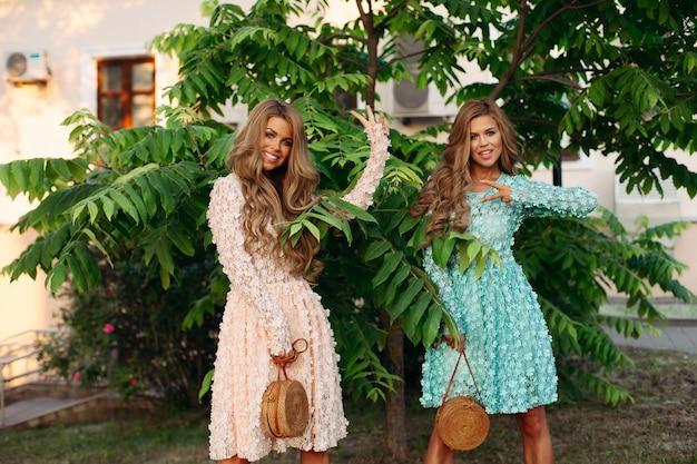 Giovani donne con lunghi capelli ondulati che tengono eleganti borse di paglia