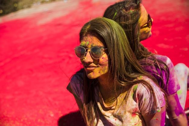 Giovani donne coperte di colori holi che indossano occhiali da sole seduti di schiena