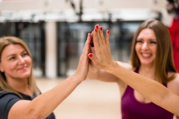 Giovani donne del primo piano felici in palestra