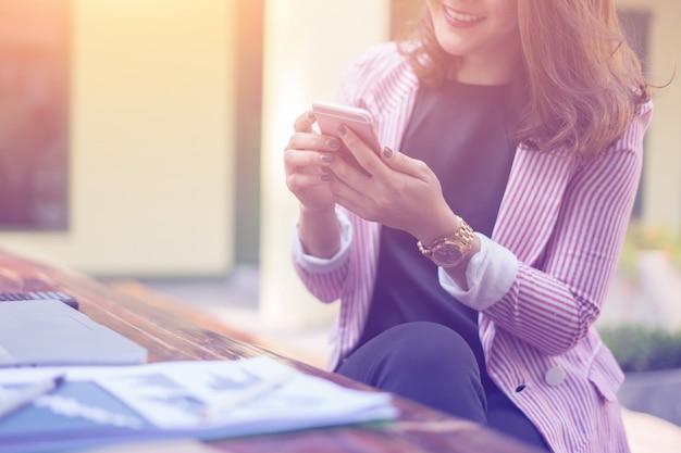 Giovani donne di affari asiatiche che si siedono all'interno e guardando smartphone