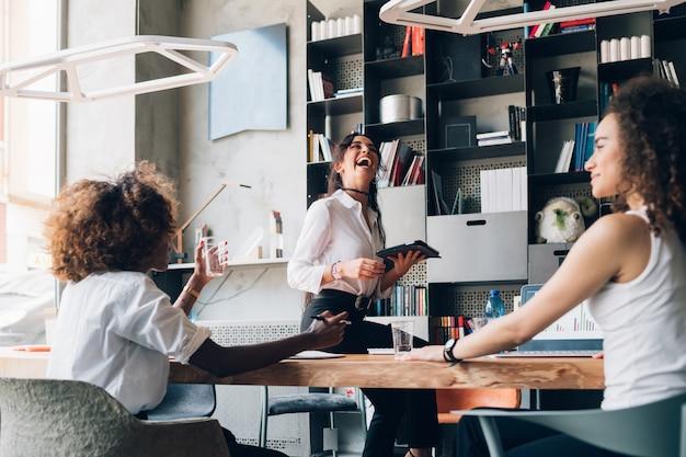 Giovani donne di affari multiculturali che hanno riunione informale in ufficio moderno