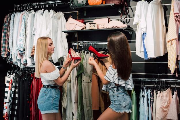 Giovani donne di angolo basso nel negozio di scarpe