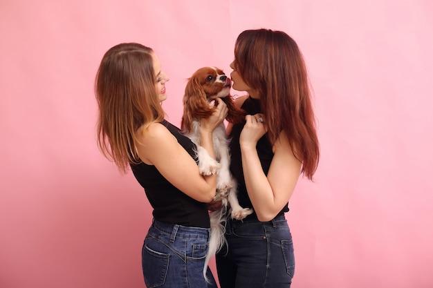 Giovani donne di modo che posano con il cane