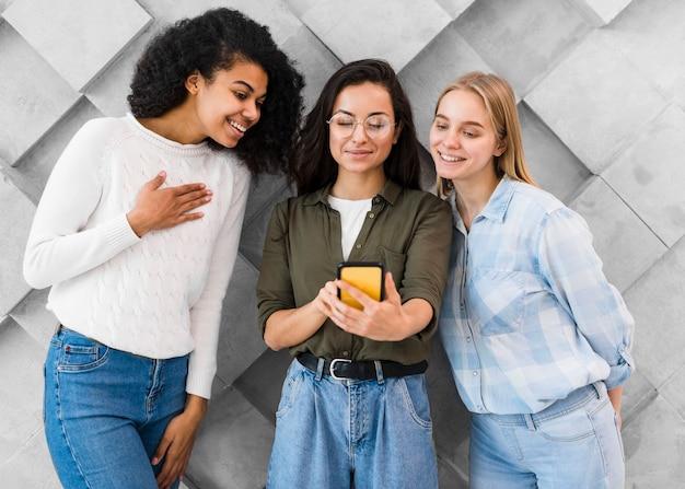 Giovani donne di smiley che prendono selfie