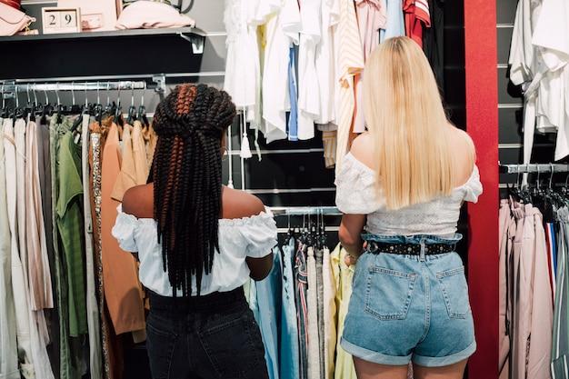 Giovani donne di vista frontale all'acquisto dei vestiti