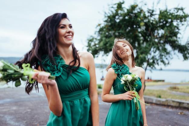 Giovani donne felici alle nozze con i mazzi di flowerrs