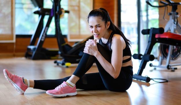 Giovani donne ferite dall'esercizio. donna adatta che ha dolore al ginocchio alla palestra
