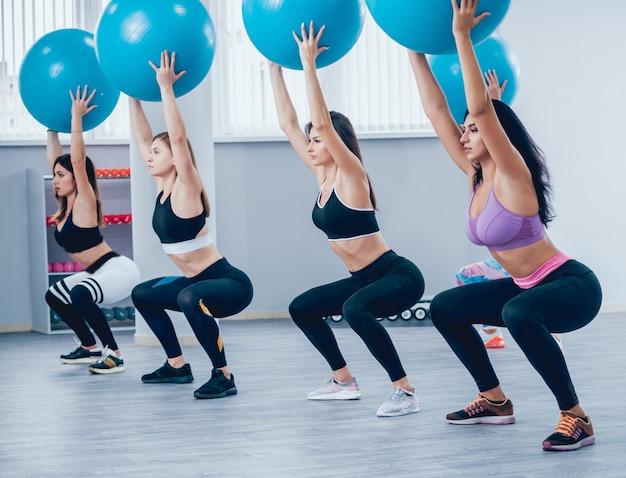 Giovani donne fitness con fitball blu. allenamento crossfit.