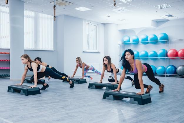 Giovani donne fitness utilizzando la piattaforma di passaggio in palestra. allenamento crossfit.