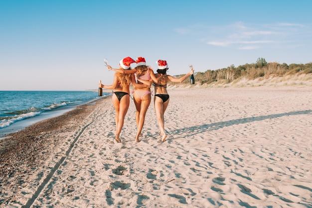 Giovani donne in bikini e cappelli di babbo natale