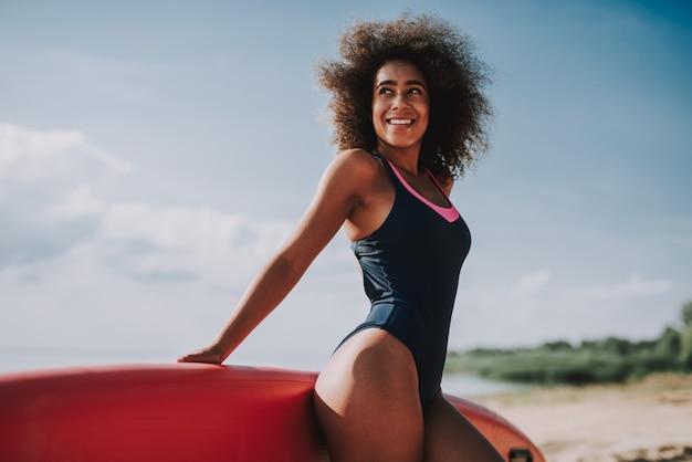 Giovani donne in costume da bagno magra su surf in spiaggia.