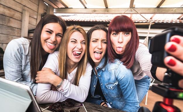 Giovani donne millenarie che prendono selfie per la piattaforma di streaming attraverso la web cam digitale d'azione