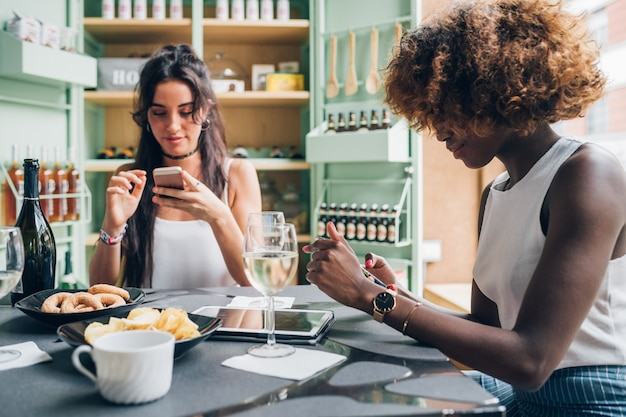 Giovani donne multirazziali che chiacchierano con lo smartphone e che si siedono in pub moderno