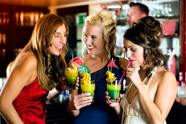 Giovani donne nel bar o club divertendosi e ridendo