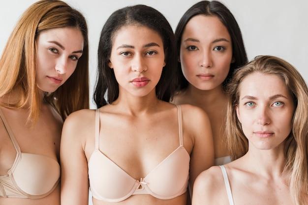 Giovani donne seri multietniche che portano i reggiseni che esaminano macchina fotografica