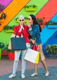 Giovani donne sorprese con le borse che bisbigliano vicino alla parete