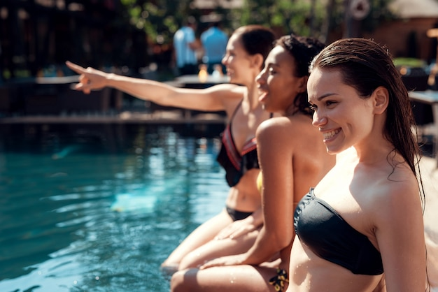 Giovani donne sorridenti che si siedono a bordo piscina