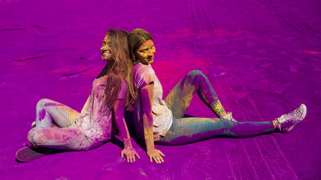 Giovani donne sorridenti che si siedono di nuovo alla parte posteriore che si siede sulla polvere di colore di holi
