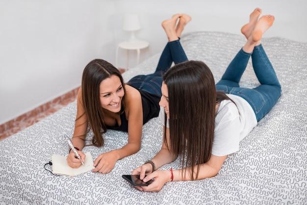 Giovani donne sorridenti che si trovano sul letto