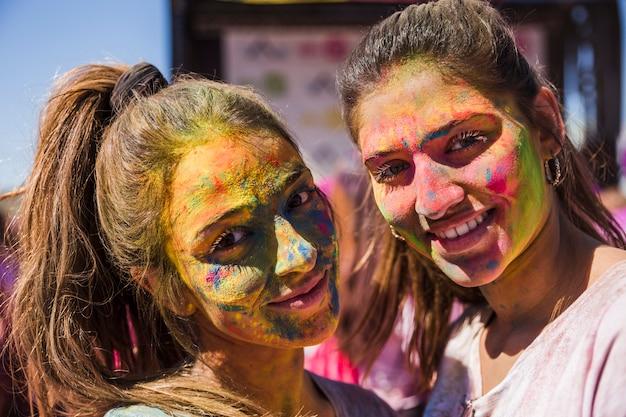 Giovani donne sorridenti con il colore di holi sul loro volto che guarda l'obbiettivo