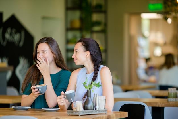 Giovani donne sorridenti felici con le tazze di caffè al caffè. concetto di comunicazione e amicizia