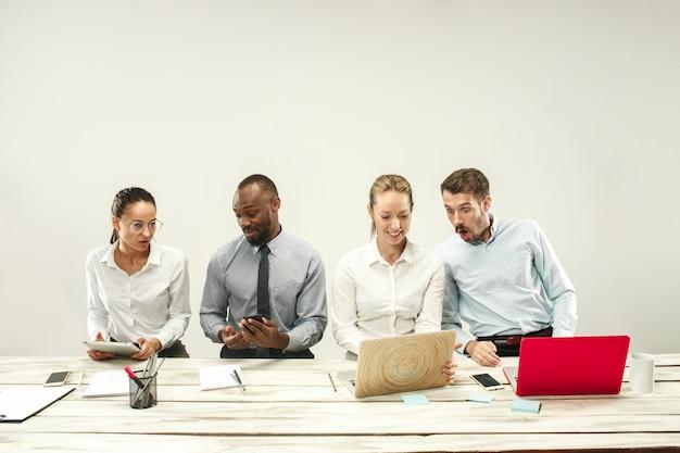 Giovani e donne che si siedono all'ufficio e che lavorano ai computer portatili. concetto di emozioni