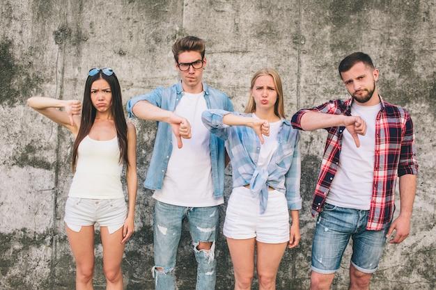 Giovani e donne tristi e infelici che mostrano i pollici giù