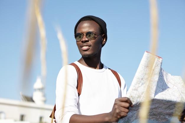 Giovani e vacanze estive. zaino in spalla africano che tiene in mano una mappa, esamina nuove direzioni del suo viaggio, sembra allegro, spensierato e assolutamente felice, si sente vivo viaggiando, indossando sfumature di specchio