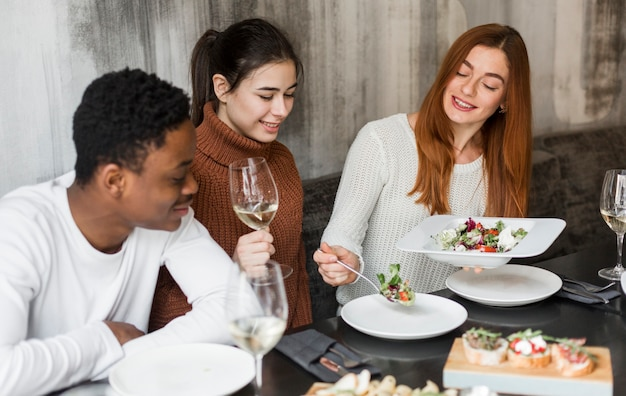 Giovani felici cenando e vino insieme