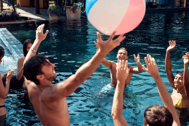 Giovani felici che giocano insieme alla spiaggia variopinta