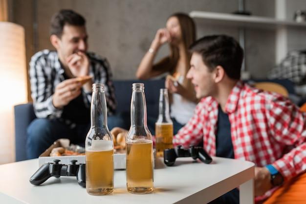 Giovani felici che mangiano pizza, bevono birra, si divertono, gli amici fanno festa a casa, compagnia hipster insieme, due uomini una donna, sorridente, positivo, rilassato, appendere fuori, ridere,