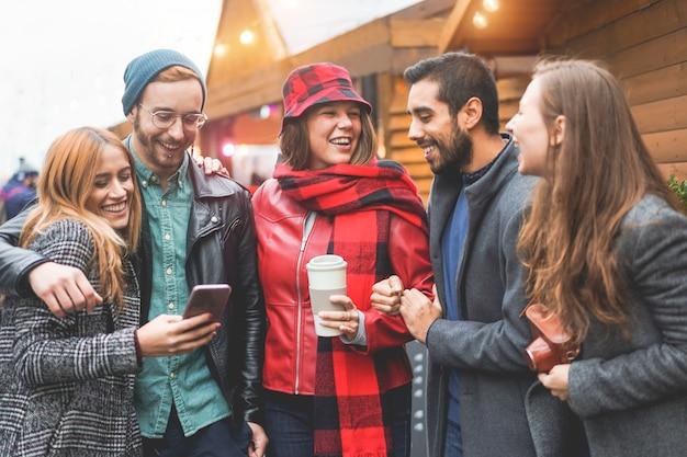 Giovani felici divertendosi al mercatino di natale durante le vacanze invernali. amici del millennial che ridono, bevono caffè e usano lo smartphone