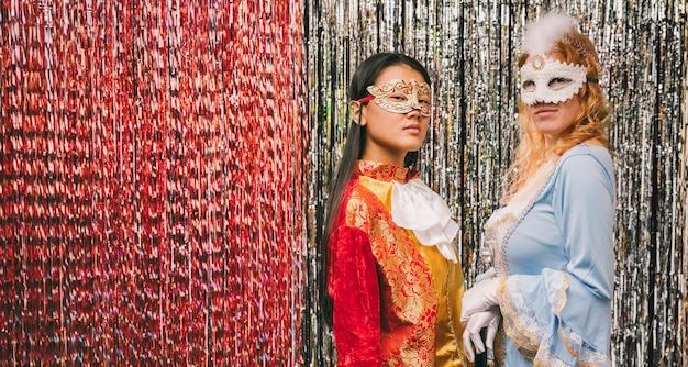 Giovani femmine con maschere alla festa di carnevale