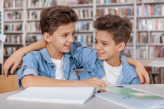 Giovani fratelli gemelli felici che ridono, abbracciando alla biblioteca mentre facendo insieme il compito di scuola