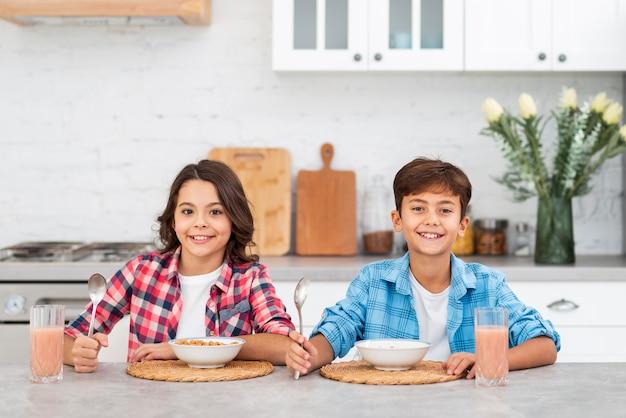Giovani fratelli germani di vista frontale che mangiano prima colazione insieme