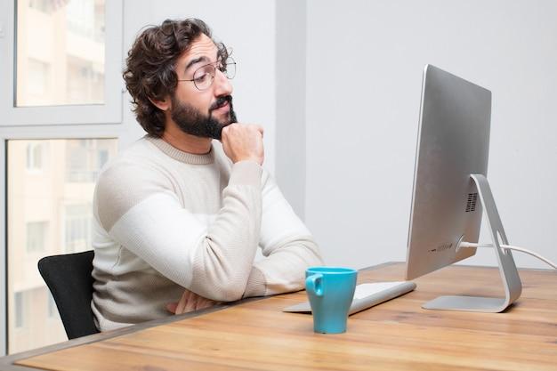 Giovani freelance pazze barbute che lavorano con il suo computer