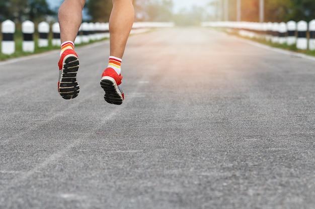 Giovani gambe del corridore dell'uomo di forma fisica che corrono sulla strada