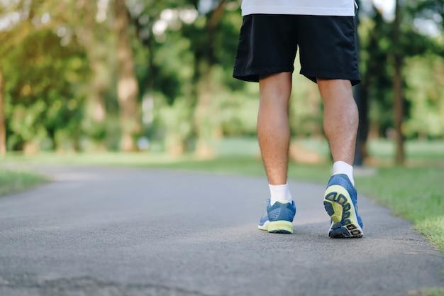 Giovani gambe dell'uomo di forma fisica che corrono nel parco all'aperto
