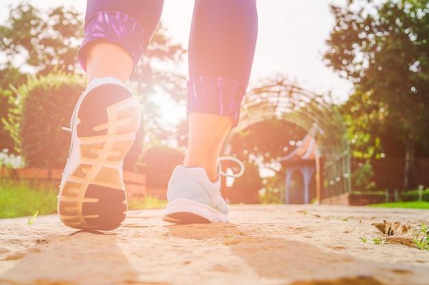 Giovani gambe della donna di forma fisica che camminano di mattina al parco pubblico all'aperto.