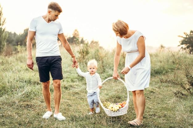 Giovani genitori con piccolo neonato sul picnic all'aperto