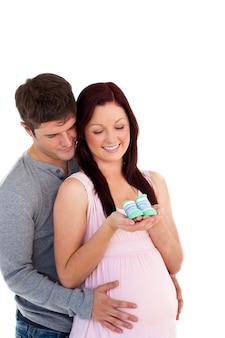 Giovani genitori futuri che esaminano i pattini di bambino contro un backg bianco