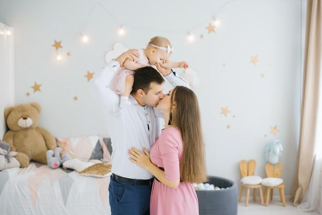 Giovani genitori mamma e papà baciano sulle labbra, la loro figlia di un anno si siede sul collo del papa e li guarda. il concetto di felicità e amore in famiglia