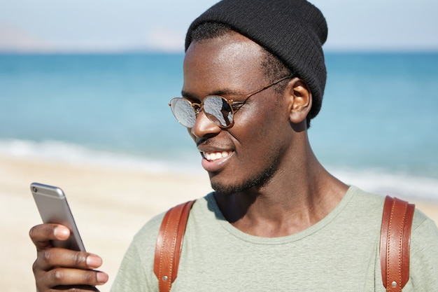 Giovani hipster dalla pelle scura alla moda con tonalità delle lenti specchiate e copricapo che leggono il messaggio o sfogliano i newsfeed tramite i social network, apprezzano i post e lasciano commenti mentre si riposa sulla spiaggia