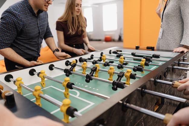 Giovani impiegati che giocano a calcio balilla