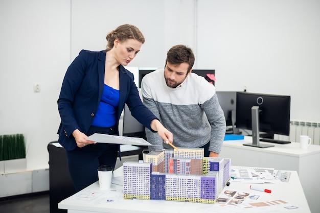 Giovani impiegati dell'ufficio di architetto che discutono il modello di costruzione