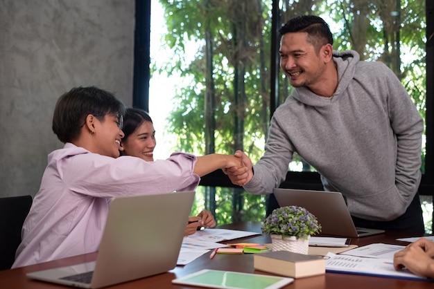 Giovani imprenditori che affondano insieme mano, riunione della squadra dei colleghi, con sentimento felice, affare di successo