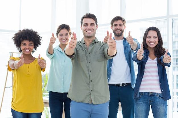 Giovani imprenditori creativi che gesturing i pollici su