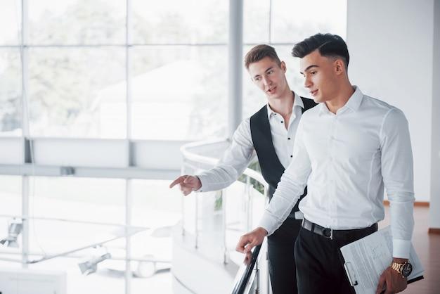 Giovani imprenditori guardando documenti e prodotti in piedi presso la ringhiera dell'ufficio