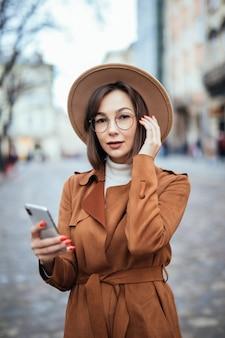 Giovani in cappello largo che manda un sms sulla via di autunno dello smartphone